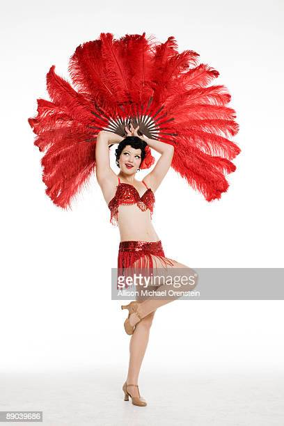 Woman posing with red feathers