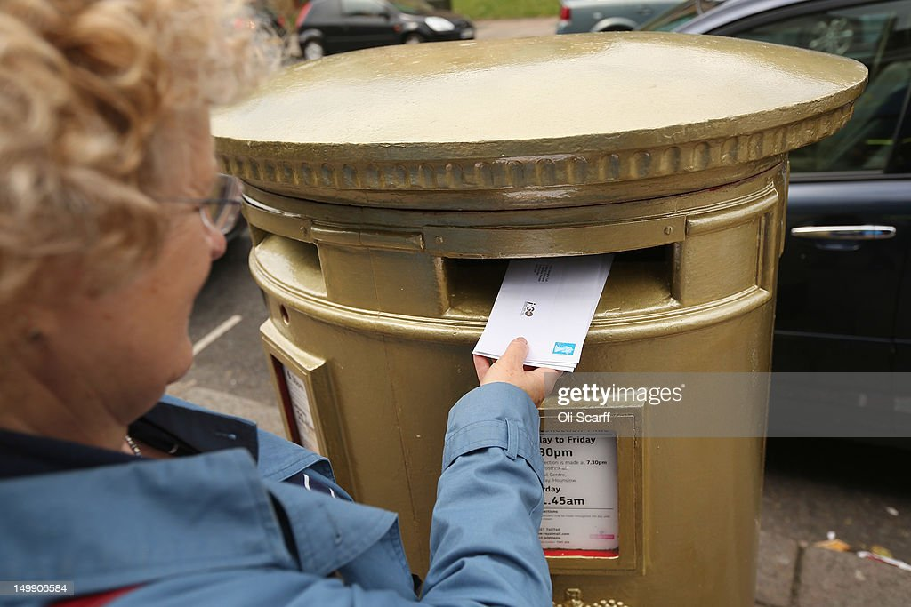 A woman post a letter in a gold post box in Isleworth on August 6, 2012 in London, England. The post box was painted gold to celebrate British athlete Mo Farah's victory in the Men's 10,000m race at the London 2012 Olympic Games on Saturday and is located close to where Mo trained and went to school.