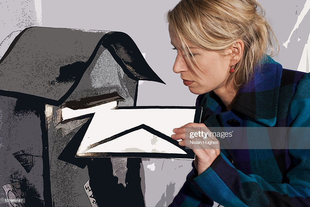 woman posting cartoon letter into mailbox. : Stock Photo