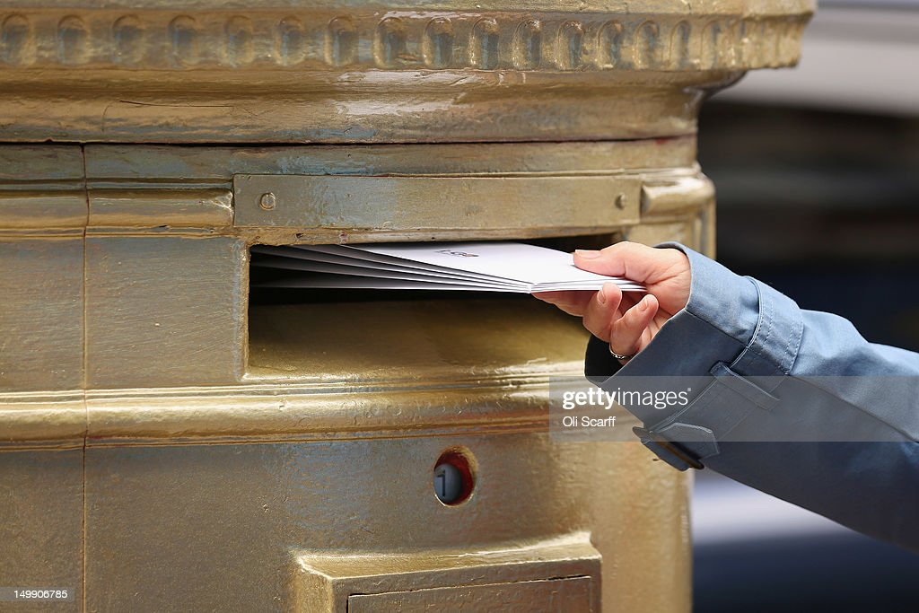 A woman posts a letter in a gold post box in Isleworth on August 6, 2012 in London, England. The post box was painted gold to celebrate British athlete Mo Farah's victory in the Men's 10,000m race at the London 2012 Olympic Games on Saturday and is located close to where Mo trained and went to school.