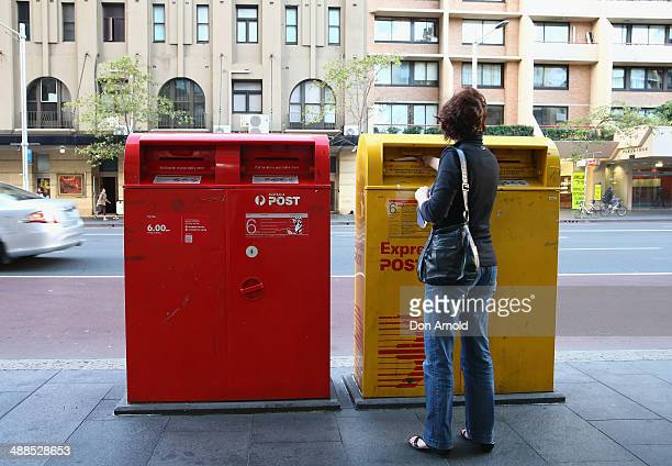 A woman posts mail via an Express Post box located on Oxford st outside the Darlinghurst Post Office on May 7 2014 in Sydney Australia Australia Post...