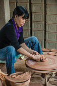 A woman potter uses a pottery wheel to fashion a piece of poetry from raw clay in rural Vietnam