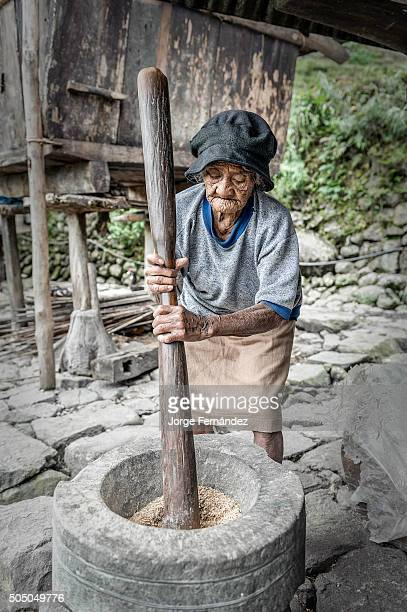 Woman pounding rice in a rural village