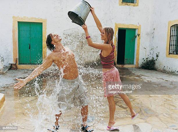 Woman Pouring a Bucket of Water Over a Man