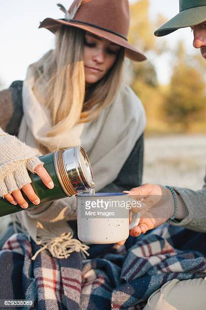 A woman pouring a hot drink from a vacuum flask into a cup on a winter picnic.