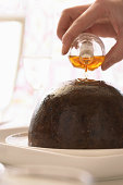Woman pouring brandy on Christmas pudding, close up