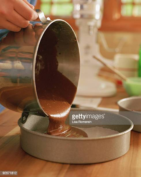Woman pouring cake batter into pan