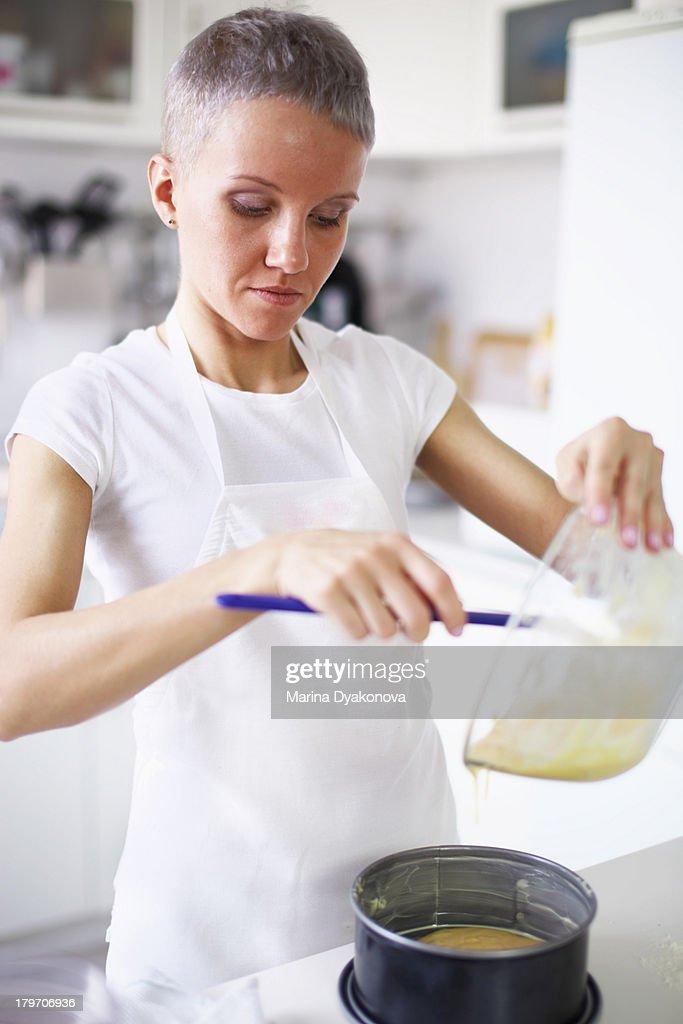 Woman pouring cake mixture into cake tin : Stock Photo