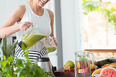 Happy woman on detox diet, pouring green cocktail from mixer into glass in kitchen