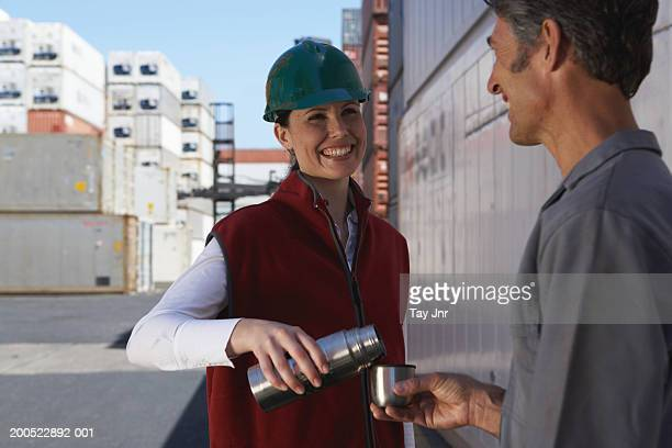 Woman pouring coffee from thermos, man holding mug, smiling
