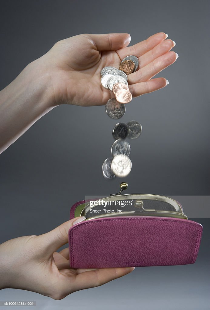 Woman pouring coins into purse, close-up of hands