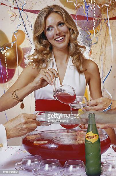 Woman pouring drink in cup and smiling at party
