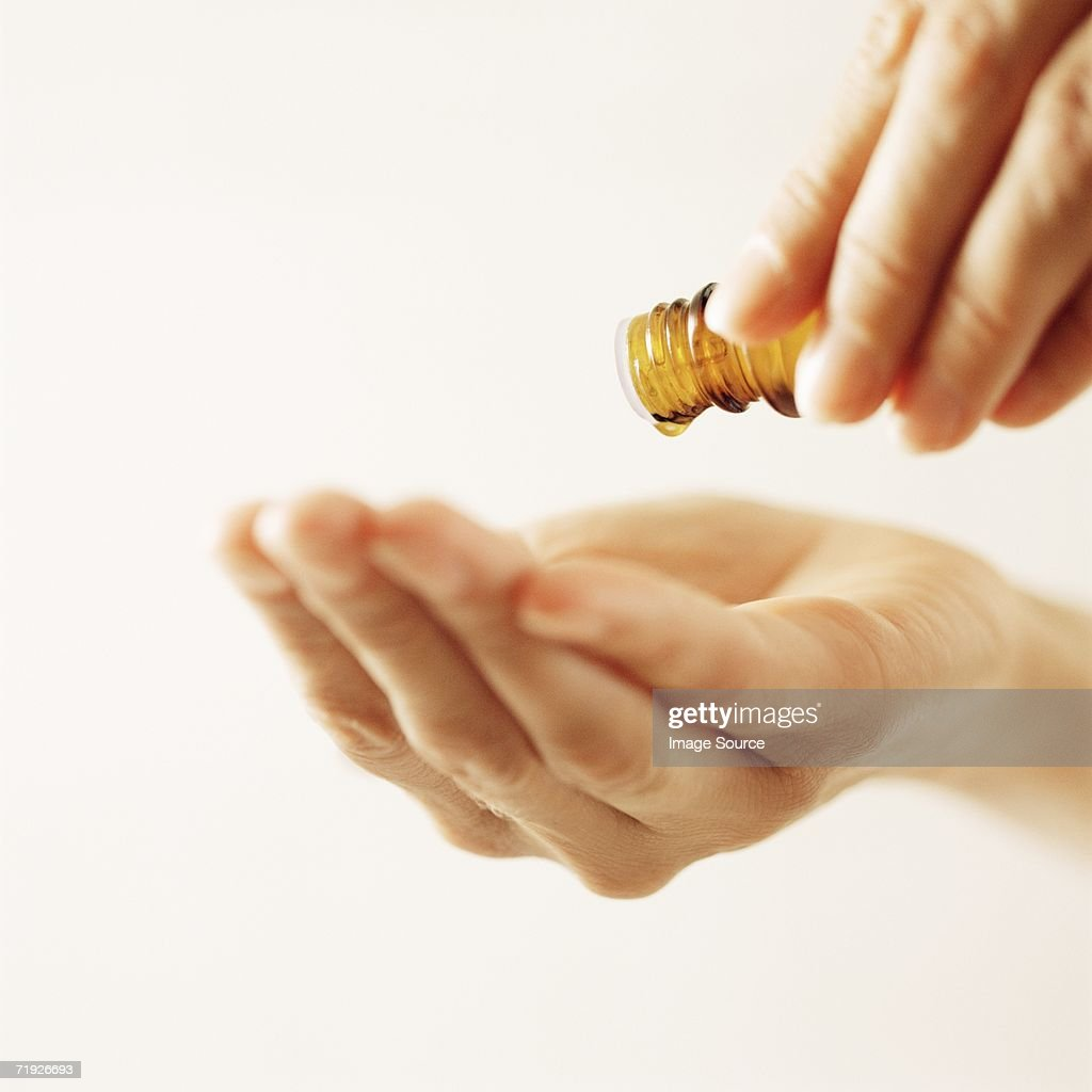 Woman pouring essential oil : Stock Photo