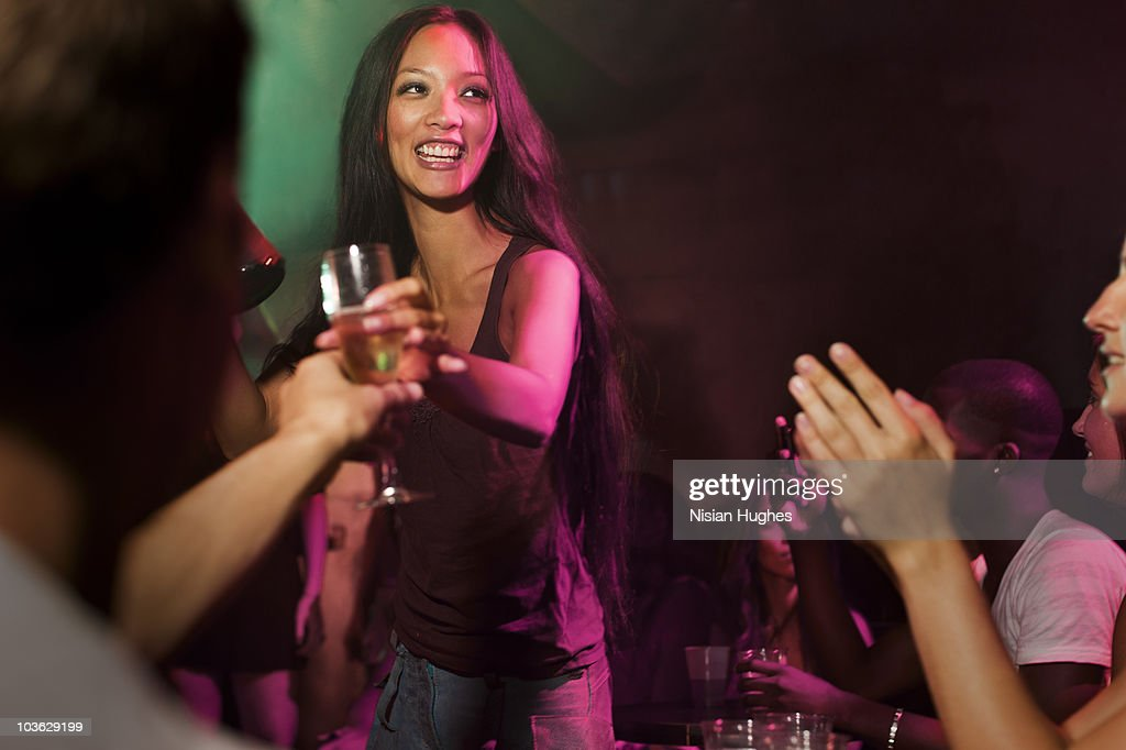 Woman pouring glass of champagne at a nightclub : Stock Photo