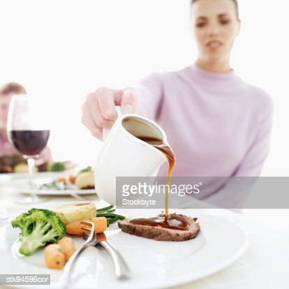 woman pouring gravy over a piece of sliced meatloaf