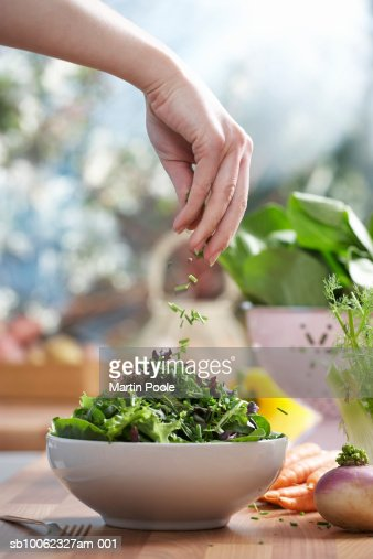 Woman pouring herbs into bowl of salad in kitchen, close-up of hand : Stock Photo