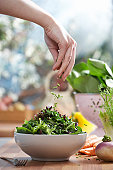 Woman pouring herbs into bowl of salad in kitchen, close-up of hand