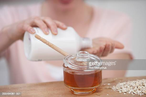 Woman pouring lotion into hand (focus on honey and oats in foreground)