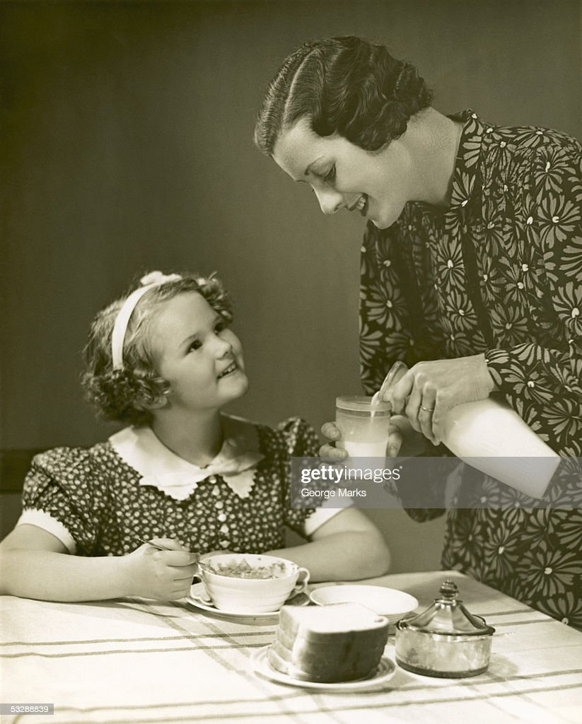 Woman pouring milk for young girl : Stock Photo