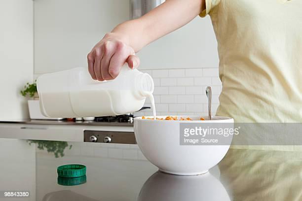Frau gießen Milch auf die Zerealien