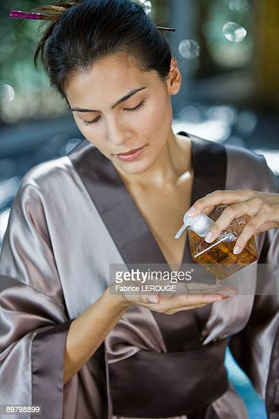 Woman pouring oil on her hand from a dispenser