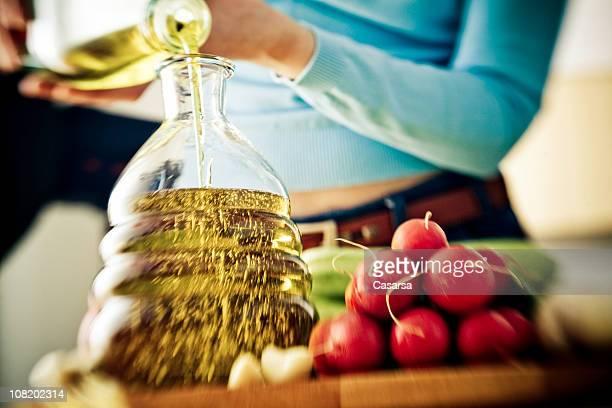 Mulher Verter azeite em frasco perto Rabanetes