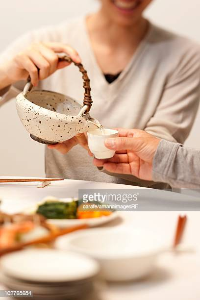 Woman pouring saki from a teapot
