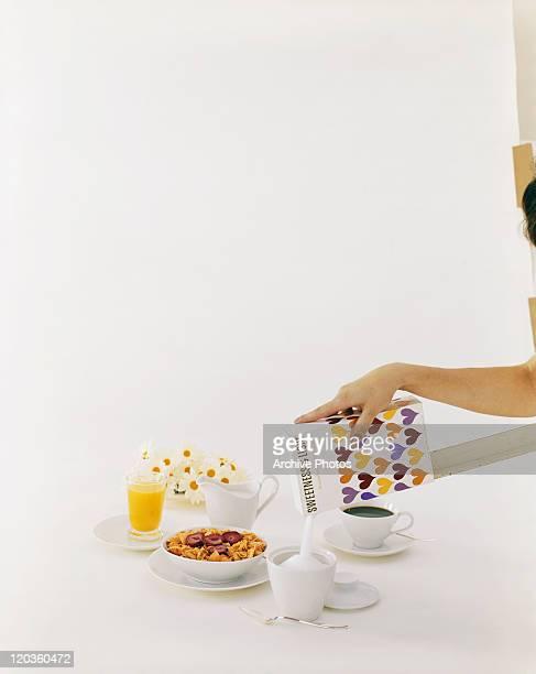 Woman pouring sugar in bowl near breakfast