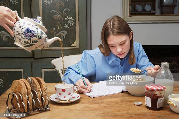 Woman pouring tea by girl (10-12) eating breakfast and writing in book