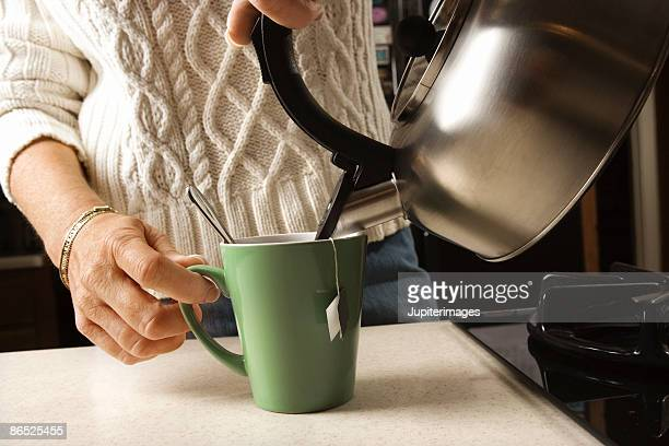 Woman pouring tea from kettle