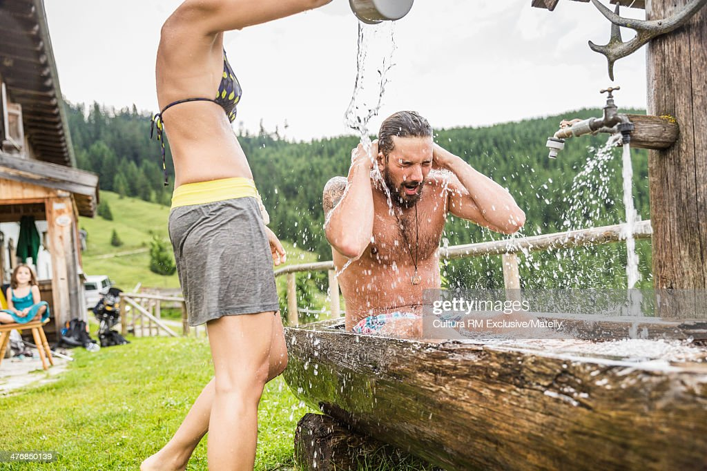 Woman pouring water over man sitting in water trough, Tyrol, Austria : Stock Photo