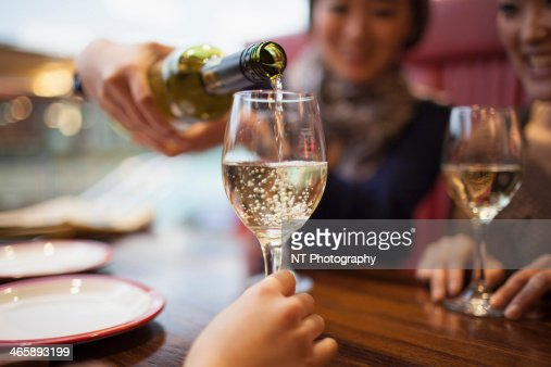 Woman pouring white wine, close up