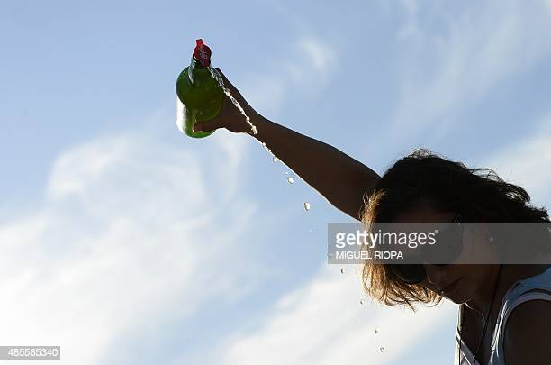 A woman pours cider as she takes part in the annual Fiesta de la Sidra Natural trying to beat the world record of simultaneous people pouring cider...