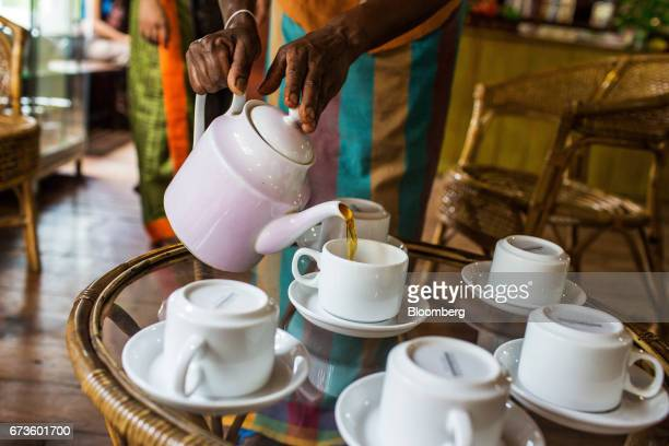 A woman pours freshly brewed tea into a cup at the Geragama Tea Estate operated by Pussellawa Plantations Ltd in Pilimathalawa Central Sri Lanka on...