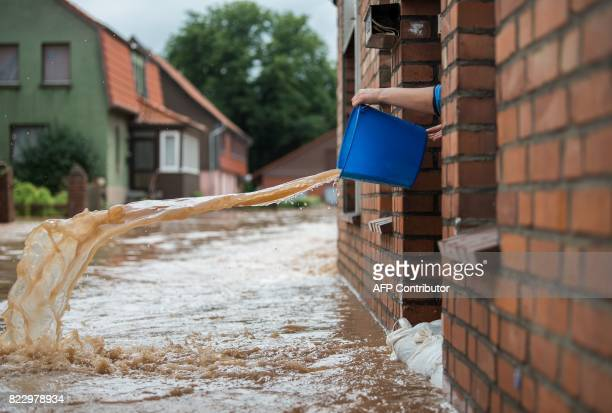 A woman pours water out of her house in Rhueden northern Germany on July 26 2017 Some parts of lower saxony are overflooded after heavy rainfall /...