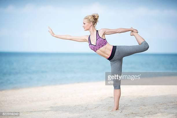 Femme praciticing un cours de Yoga sur la plage
