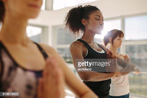 Mujer la práctica del yoga con amigos en el gimnasio : Foto de stock
