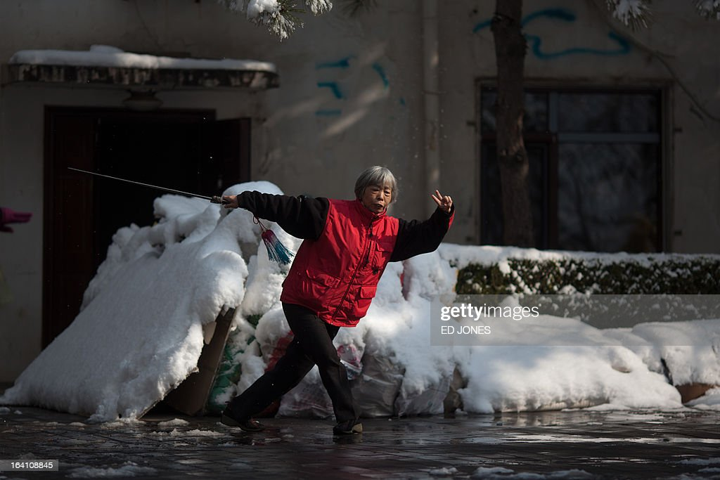 A woman practices a sword routine inside a park following overnight snowfall in Beijing on March 20, 2013. Beijing and the north of China has been experiencing its coldest winter in more than 30 years and has seen tens of thousands of the countries livestock dying and transport chaos as flights and highways are shutdown. AFP PHOTO / Ed Jones