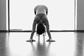 Female yogi in downward facing dog asana. Natural light, floor reflection, workout, minimal concepts. Black and white photography