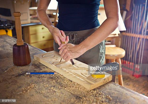 Woman Practices Carving on a Scrap Piece of Wood.