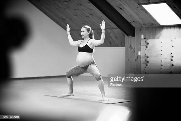 Woman practices goddess pose in prenatal yoga