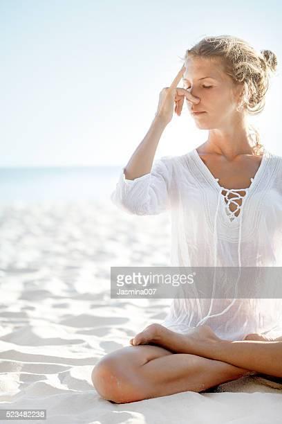 Femme en posture de lotus pratiques pranayama sur la plage