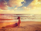 Vintage retro effect filtered hipster style image of Yoga outdoors on beach - woman practices Ashtanga Vinyasa yoga Surya Namaskar Sun Salutation asana Urdhva Mukha Svanasana - upward facing dog pose