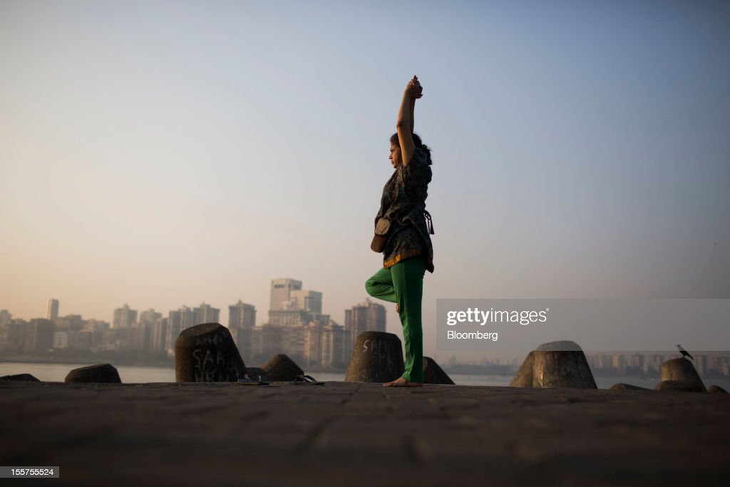 A woman practices yoga in front of the Nariman Point skyline in Mumbai, India, on Tuesday, Nov. 6, 2012. Reserve Bank of India Governor Duvvuri Subbarao lowered the RBI's forecast for India's gross domestic product growth in the year through March to 5.8 percent, the slowest in almost a decade, from 6.5 percent. Photographer: Brent Lewin/Bloomberg via Getty Images