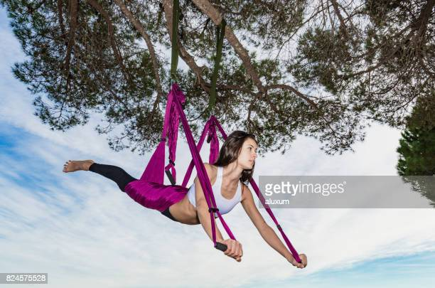 Woman practicing aerial yoga hanging from a tree