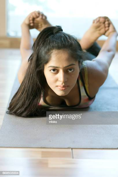Woman practicing bow yoga pose