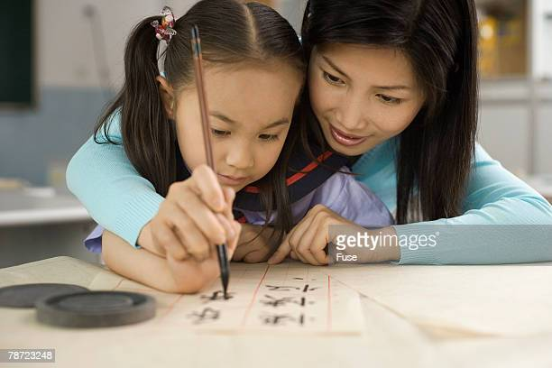 Woman Practicing Calligraphy with Girl