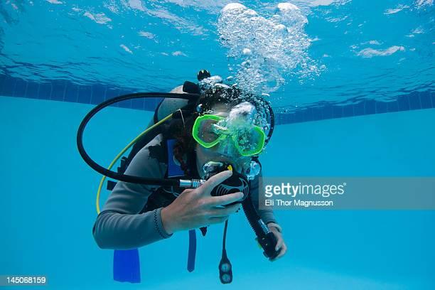 Woman practicing scuba diving in pool