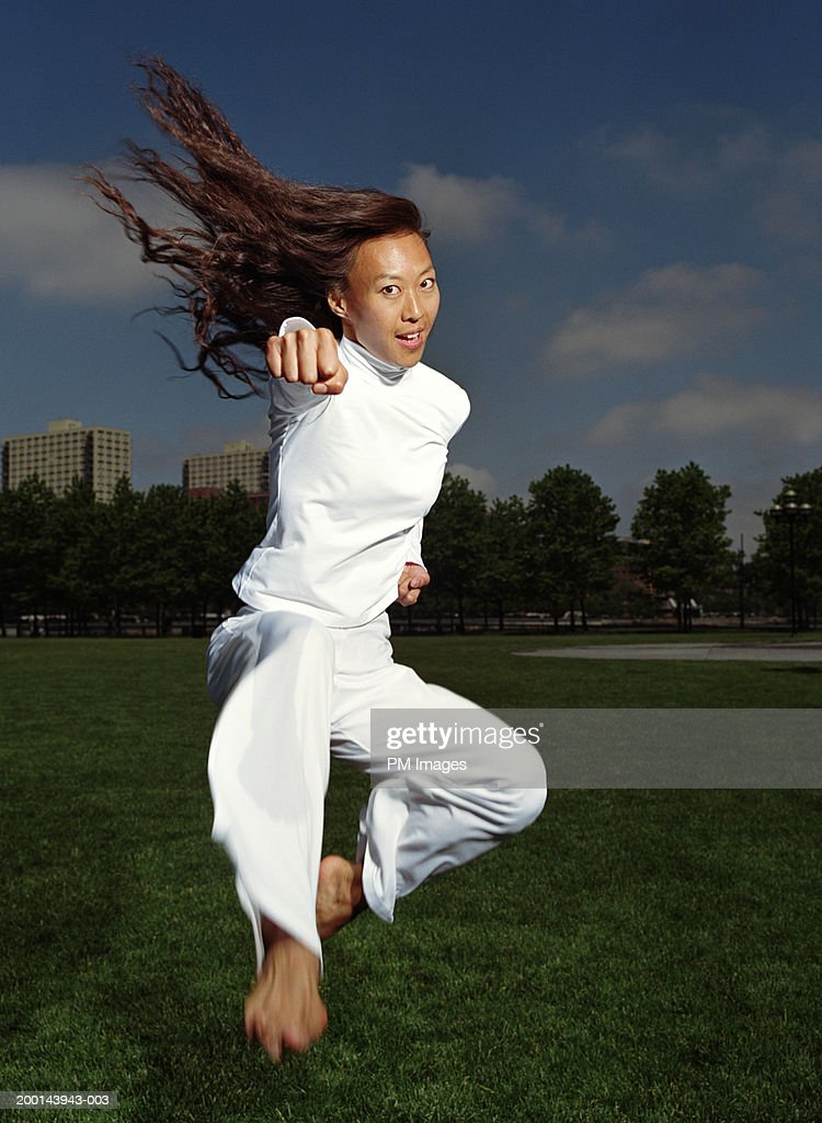 Woman practicing tae kwon do in park (blurred motion) : Stock Photo