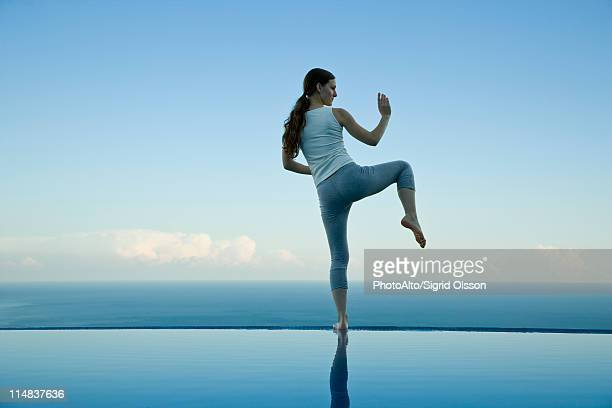 Woman practicing Tai Chi Chuan on edge of infinity pool